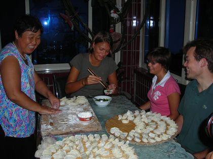 Sarah, Géraldine et Cédric suivent un cours de cuisine chinoise. Ils font des raviolis sous le regard amusé de leur professeur du jour.