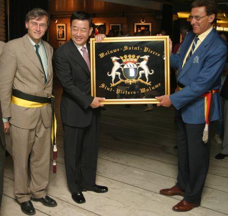 Le bourgmestre Jacques Vandenhaute et l'échevin des jumelages Serge de Patoul,  pour Woluwe-Saint-Pierre offrent au maire Monsieur Kwon Moon Yong pour Gangnam les armoiries brodées.