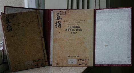Un fac-similé du premier livre imprimé par un processus d'imprimerie (l'anthologie des enseignements des prêtres Zen du grand Bouddhisme) donné par Gangnam à Woluwe-Saint-Pierre et mis en dépôt à la bibliothèque Wittockania